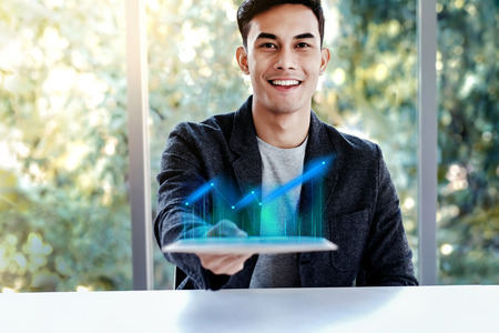 Technology in Business Concept. Happy Young Man Sitting at the Desk and presenting High Profit Graph in Digital Tablet. Smiling and Looking at Camera
