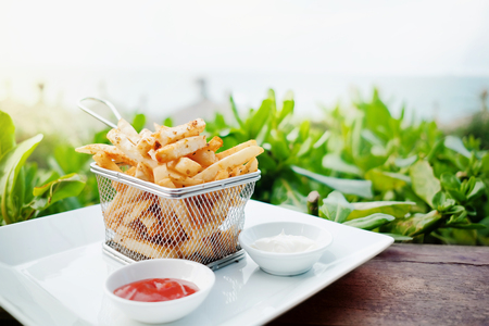 French Potato Fries on Metal Mesh Flying Sieve with Two Dipping Sauce, Served on Rustic Wooden Table in Outdoor