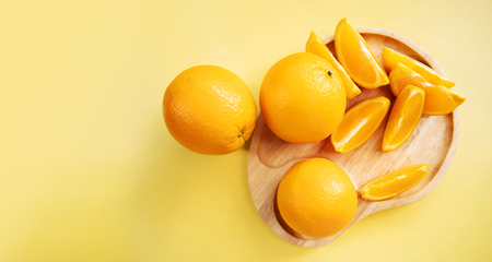 Sliced Orange on Wooden Plate. Fresh Juicy Fruit in Summer. Top View. Flat Lay on Yellow bcakground