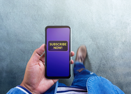 Subscribing and Digital Marketing Concept. Top View of a Man using Smartphone to making Subscribe on his Favorite Channel. Media Content Strategy