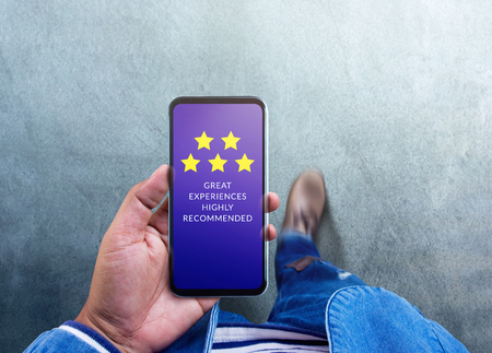 Customer Experiences Concept. Five Stars Rating and Positive Review show on Smartphones Screen. a Modern Man Reading Clients Satisfaction Surveys via Mobile Phone. Top View Stok Fotoğraf