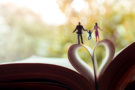 Love and Happy Family. Work Life Balance Concept. Miniature of Father, Mother and Son holding Hands and Walking toward the Book over a Page Roll like Heart Shape