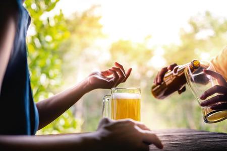Freundschaftskonzept. Zwei Freunde trinken Bier und unterhalten sich im Sommer über ein Thema auf dem Balkon