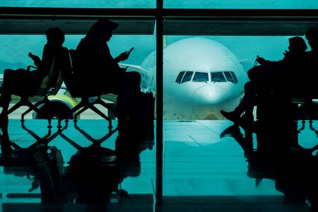 Silhouette of many Passengers Waiting for Boarding in Departure Terminal in the Airport. Airplane as background