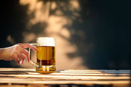 a Glass of Beer on Table in Summer Sunny Day. People Drinking Brew. Shadow of Tree as background