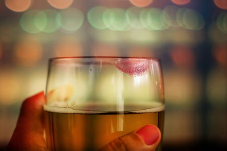 Woman Drinking Beer Concept. Closeup of Glass of Beer with Red Lipstick Mark in Bar or Restaurant. Feminine Mood 写真素材