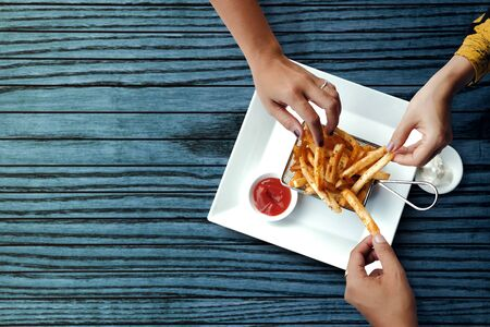Three Friends Eating French Potato Fries, Serve on Metal Mesh Flying Sieve with Two Dipping Sauce. Lay on Wooden Table. High Angle Top View Shot Stok Fotoğraf
