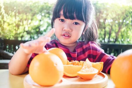Fruit and Vegetable for Kids Concept. Little Cute 3-4 Years Old Girl with Sliced Orange on Wooden Plate. Fresh Juicy Fruit in Summer