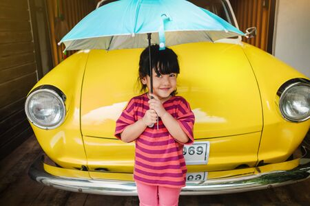 Portrait of Happy Kids with an Umbrella before Outing. Protecting Rain or Sunlight in Summer or Rainy Season Concept. Cute 3-4 Years Old Girl in Happiness Moment.Looking at Camera