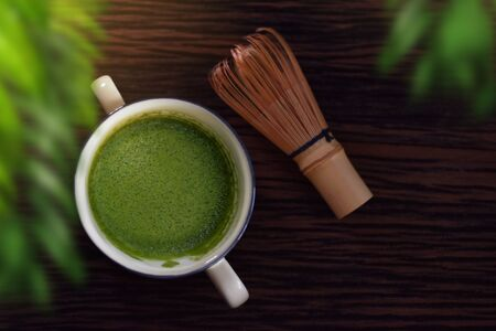 Hot Matcha Green Tea Latte Cup on Wooden Table with Chasen or Bamboo Whisk. Japanese Traditional Drink. Blurred Green Leaf as foreground. Top View 写真素材