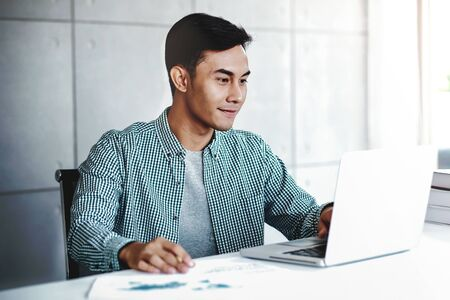 Happy Young Businessman Working on Computer Laptop in Office