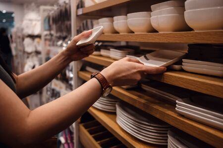 Customer Compared Products from Rack in the Shop. Young Woman Choosing Dishware in Household Store. Croped image