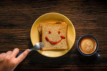 Happy Life concept. Young Person Eating Bread and Coffee Cup in Breakfast Time. Smiling Face Drawn on Bread. Top View