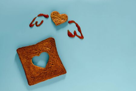 Love and Freedom Concept. Flat Lay of Sliced Toasted Bread in Shape of Heart and Wings Drawn by Tomato Sauce. Top View