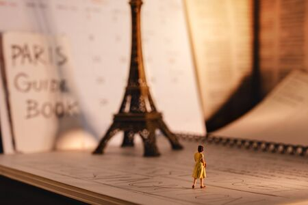 Dream Destination for Vacation. Travel in Paris, France. a Miniature Tourist Woman Looking at the Eiffel Tower and Calendar. Warm Tone. Vintage Style