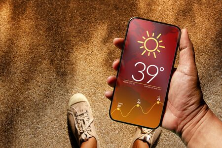 Ecology and Technology Concept. High Temperature Weather show on Mobile Screen on Hot Sunny Day. Top View, Grunge Dirty Concrete Floor with Sunlight as background Stok Fotoğraf