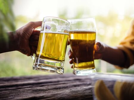 Two Friends making Cheers with Glasses and Drinking Beer at the Balcony in Summer Stok Fotoğraf