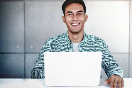 Smart Young Asian Businessman Working on Computer Laptop in Office. Smiling and looking at Camera Фото со стока