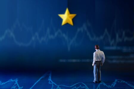 Success in Business or Talent Concept. a Miniature Businessman standing on Financial Graph and Looking on the wall with Yellow Golden Star