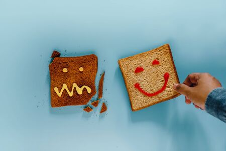Happiness lifestyle concept. Flat Lay of Sliced Toasted Bread. Person Picked a Well Done Piece with Smiling Face. the Burned one with Crazy Face is not Select. Top View