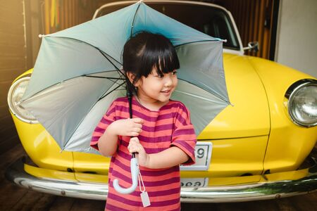 Portrait of Happy Kids with an Umbrella before Outing. Protecting Rain or Sunlight in Summer or Rainy Season Concept. Little Cute 3-4 Years Old Girl in Happiness Moment.