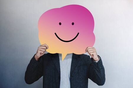 Customer Experience or Human Emotional Concept. Man Presenting his Happy Feeling by Drawn Line Cartoon Face on Speech Bubble Card