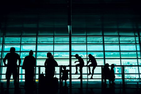 Travel with Kids Concept. Silhouette of a Big Family Passengers Waiting for Boarding in Departure Terminal in the Airport