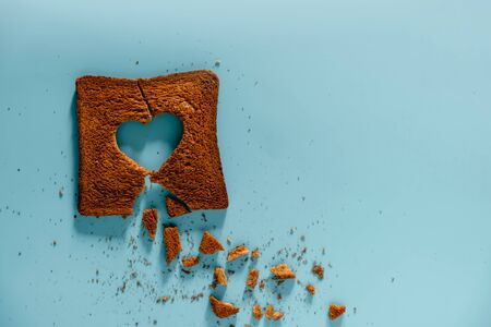 Unhappy Relationship concept. Flat Lay of Burned Sliced Toasted Bread with a shape of Broken Heart. Top View