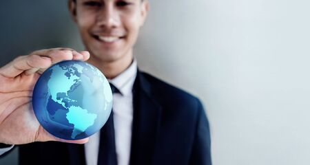Globalization and Worldwide Concept. Happy Smiling Professional Businessman holding a Transparent Blue World Globe in Hand