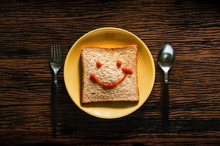 Happy Life concept. Bread on Plate with Spoon and Fork for Breakfast Time. Smiling Face Drawn on Bread. Top View Reklamní fotografie