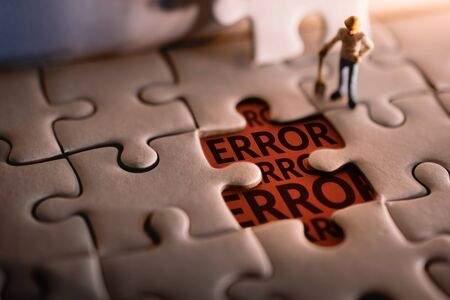 Solution Solving Problem Concept. a Miniature Worker Man Found Error Message on a Piece of Jigsaw Puzzle