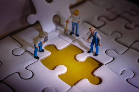 Teamwork and Solving Problem Concept. Group of Miniature Worker Men Found Something Wrong on the Work Process (a Piece of Jigsaw Puzzle) 写真素材 - 129453675