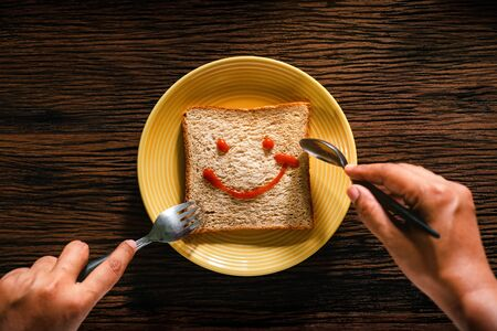Happy Life concept. Young Person Eating Bread in Breakfast Time. Smiling Face Drawn on Bread. Top View