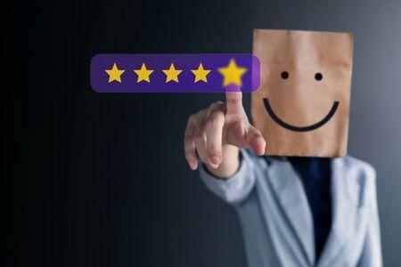 Concepto de experiencias del cliente. Mujer de negocios feliz con cara sonriente en bolsa de papel dando cinco estrellas por su satisfacción. Comentarios y revisión del cliente Foto de archivo