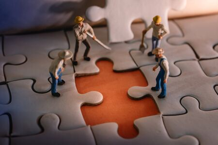Teamwork and Solving Problem Concept. Group of Miniature Worker Men Found Something Wrong on the Work Process (a Piece of Jigsaw Puzzle) 写真素材 - 129456170