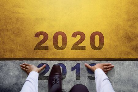 2020 jaarconcept. Bovenaanzicht van zakenman op startlijn, klaar voor nieuwe zakelijke uitdaging