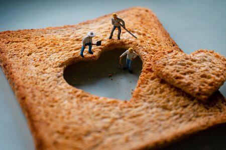 Liebe Konzept. Traurige Beziehung. Gruppe von Arbeitern Miniatur, die ein gebranntes geschnittenes Toastbrot mit einer Herzform repariert