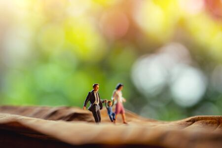 Love and Happy Family. Work Life Balance Concept. Miniature of Father, Mother and Son holding Hands and Walking on Dry Leaf in Park