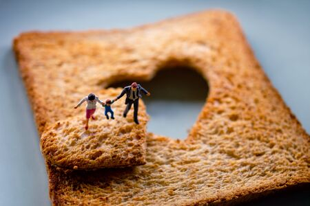 Love Concept. Miniature of Happy Family Walking on Burned Sliced Toasted Bread with a shape of Heart Reklamní fotografie