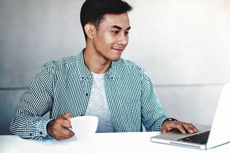 Happy Young Businessman Working on Computer Laptop in Office. Smiling and looking at Computer Reklamní fotografie