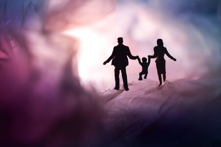 Love and Happy Family. Exploration for Children and Parent. Miniature of Father, Mother and Son holding Hands and Walking on a Mystery Dark Place Banco de Imagens
