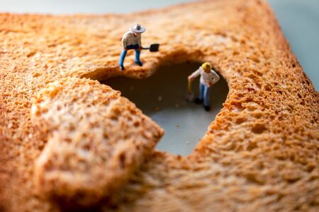 Love Concept. Sad Relationship. Group of Worker Miniature Fixing a Burned Sliced Toasted Bread with a shape of Heart Banco de Imagens