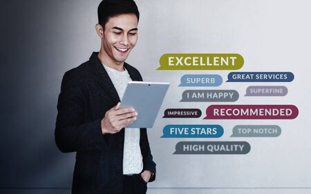 Customer Experiences Concept. a Young Happy Man Reading Positive Review Rating via Digital Tablet. Clients Satisfaction Surveys Online