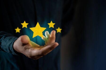 Concepto de experiencias del cliente. Persona que da una opinión positiva de las encuestas de satisfacción del cliente. Calificación de cinco estrellas flotando en la mano. Tono oscuro