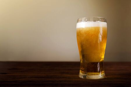 Glass of Beer on Wooden Table. Front View. Shot with Natural Daylight