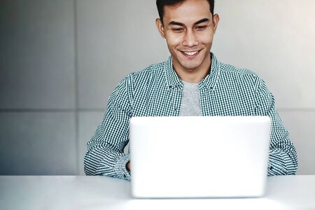Happy Young Businessman Working on Computer Laptop in Office. Smiling and looking at Computer Screen