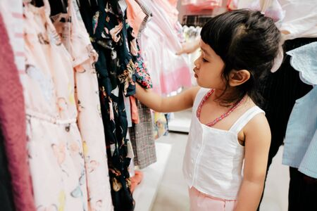 Soft Focus of a 4-5 Years Old Child Choosing her own Dresses from Kids Cloth Rack in Clothing Shop. Shopaholics Girl