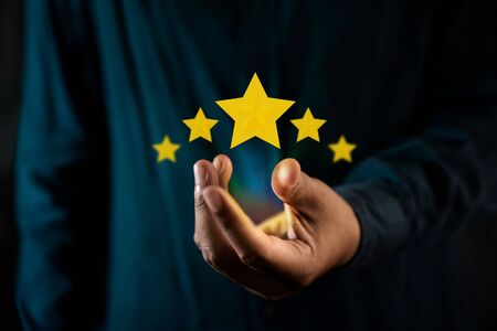 Customer Experiences Concept. Person Giving Positive Review for Client's Satisfaction Surveys. Five Stars Rating floating on Hand. Dark Tone Standard-Bild