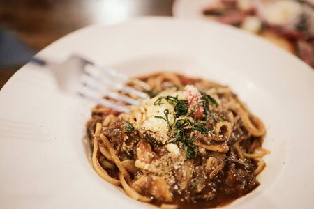 Eating Spaghetti Beef Sauce in Restaurant at Night.Selective Focus Banco de Imagens