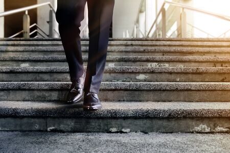 Motivation and challenging Career Concept. Steps into a Success. Low Section of Businessman Walking Down on Staircase. Male in Black Formal Dress